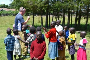 Patrick McKennon entertaining children in Chebunyo